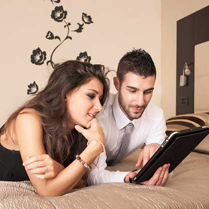 A couple standing on the bed of a motel room while using a tablet connected to a wifi hotspot software.