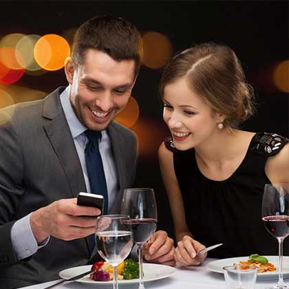 A couple having dinner in a restaurant while using a smartphone to connect to a Wifi hotspot.