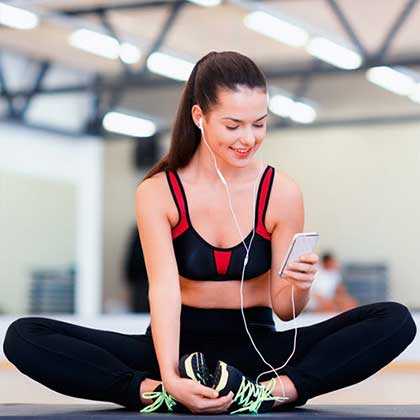 A woman doing stretching activities into a gym while using her smartphone to connect to a Wifi Hotspot.